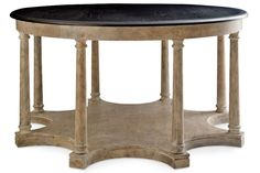 """Mary McDonald's Drayton center table for Chaddock is crafted of oak in a dappled grey finish with an oxford black–finished top, 64"""" dia. x 34"""" h.; $16,497. chaddockhome.com"""