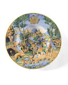 """URBINO Plat circulaire en faïence décoré en polychromie d'une scène mythologique """"en plein """" représentant CADMUS tuant le dragon entouré d'hommes en armes. Un guerrier à terre. Au fond, une ville (Thèbes ?) dans un paysage au bord de l'eau. Armoiries sur l'aile sur Montées d'un heaume, encadrées de trois tortues avec la devise """"BPAAYTHE """". Seconde moitié du XVIème sièclecirca 1560/1570."""