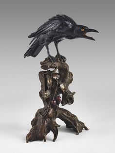 Japanese bronze crow perched on a tree trunk, with inlaid glass eyes, signed in an oval reserve Kazan saku 華山作, Meiji Period.  In Japanese mythology crows are thought to be gifted with supernatural powers and are also messengers of the gods.