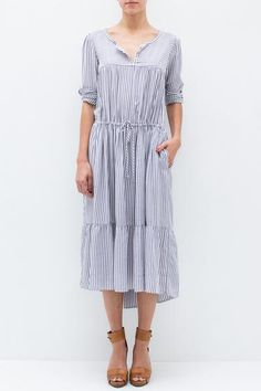 "- 100% Rayon - Split neckline with 3 button closures - Drawstring waist - Tiered bottom - Pleated chest - Side seam pockets - Unlined - Color: Blue/White Stripe - Model is 5'9"" and wears a size Petite"