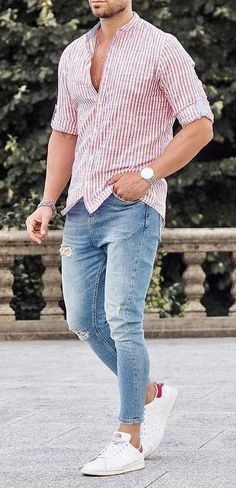 27f59afd36cd40 Men s red and white untucked button down shirt with blue jeans and white  sneakers.