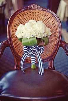 White bouquet wrapped with blue and white striped ribbon