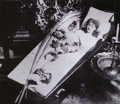 """The Great Sarah Bernhardt Asleep in Her Coffin, Silver gelatin print, circa 1882 Bernhardt (1844-1923) made her own funeral arrangements. She picked out her own coffin because she was going to """"sleep"""" in it forever. She had it delivered to her home and regularly slept in it. In her 1907 autobiography she wrote, """"My bedroom was very tiny. The big bamboo bed took up all the room. In front of the window was my coffin, where I frequently installed myself to learn my lines."""""""