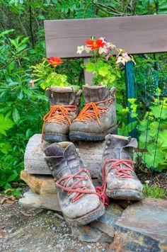 Ein paar verwaschen Arbeit, die Stiefel als Blume Pflanzer zu dienen, während ein anderes Paar eine noch verwaschen Stiefel ihrerseits reaktiviert werden erwartet. Die bunten Schnürsenkel beide Stiefel hinzufügen seine verblichenen Umwelt Kontrast.