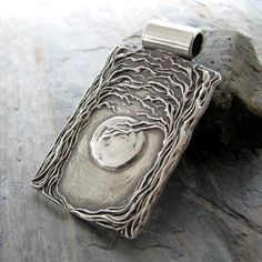 A substantial and stunning pendant in fine silver, pressed in recycled 99.9% pure silver from my original carving. After sketching the design, I carved it carefully into a lino block. I love the intricate detail and texture of the trees. The trees seem to be reaching out to each other and frame the moon beautifully. This is a piece of art to wear. Engraving on the back is included; up to 20 characters. At checkout, there will be a message box for the personalization information.  Pendant is…