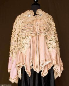"""Wool and lace cape, English, 1890's; Faun wool flannel, overlay of ecru Battenburg lace with narrow brown velvet curlicue designs over lace, handkerchief hem points, embroidered lace collar with front puffs and pair of rhinestone buckles at back; Center back length: 33"""""""