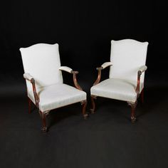 """Chippendale Gainsborough Chairs This handsome carved mahogany library or """"Gainsborough"""" armchair has a gently curving back and shaped arms which have acanthus leaf carved scrolled handles and leaf carved moulded supports. The padded seat is raised on moulded cabriole legs decorated with carved cabuchons, leaves and scrolls and strand on tightly scrolled toes.   40.75"""" High, 27.5"""" Wide, 25"""" Deep"""