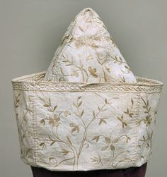 Men's Undress Cap, England, early 18thC. his cap was made from four triangular quadrants of white cotton, embroidered identically with stylized branches, blossoms, and leaves and accented with a border of serpentine guilloche on the wide up-turned brim. The separate pattern pieces were first embroidered on one side, and then flipped over and worked on the other so that the embroidery would show around the entire circumference of the cap with a minimum of cutting.   Cora Ginsburg