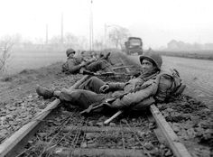 """During the Battle of the Bulge, U.S. soldiers of the 104th Infantry """"Timberwolf"""" Division rest on the rails after combat in Dürenin in North Rhine-Westphalia, Germany (December 21, 1944)."""