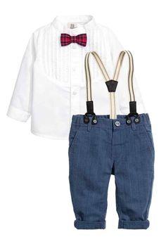 Chemise et pantalon: Ensemble composé d'une chemise et d'un pantalon en coton. Chemise en popeline avec petit col droit et plastron avec plis nervure décoratifs au niveau de la poitrine. Nœud papillon cousu devant. Pantalon avec élastique réglable à la taille et fausse braguette avec bouton. Poches latérales et une fausse poche dans le dos. Bretelles élastiques, assorties et réglables.