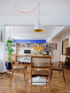 Sala de jantar integrada ao estar e escritório com mesa saarinen e cadeiras com acabamento em palhinha.