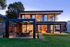 Szép vízparti környezetben épült modern kétszintes ház szimpla formákkal. A szögletes blokkok, a belső és külső terek között folyamatos, könnyed a kapcsolat, a tágas lakóterek és a teraszok, kert egysége tökéletes. Az utcafront felől szolid, mégis érdekes képet mutat a ház a cédrusfa borítással, melyen látványos a vízszintes és függőleges fa elemek és a világos felületből kiugró sötét ablakkeretek kontrasztja.