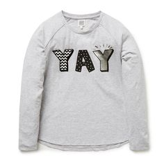 100% Cotton tee. Long sleeve t-shirt features front placement slogan 'Yay' with glitter and foil accents. Regular fitting silhouette. Available in Cloud.