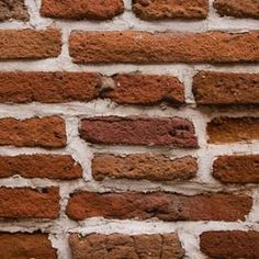 Inserting nail into a brick wall requires the correct procedure and tools.