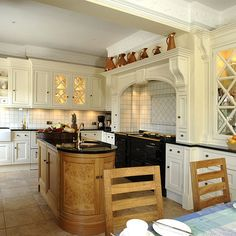 Cream kitchen white tiled alcove solid wood fitted units mantel Aga cooker surround curved solid wood oval island fitted unit glass door cabinets black granite worktop round circular sink glas door cupboards dining area table real home BK 02/2008