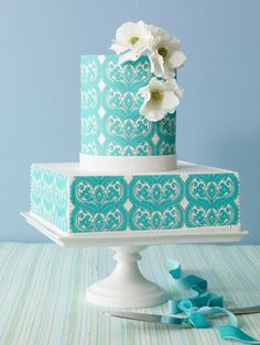 Teal-patterned and printed fondant wedding cake accented with sugar flowers and white trim by Bijoux Doux