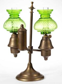 """EUROPEAN BRASS DOUBLE-ARM MINIATURE STUDENT LAMP EUROPEAN BRASS DOUBLE-ARM MINIATURE STUDENT LAMP, weighted circular foot supporting a central vertical shaft with finial extension, conical-form fonts and a single cylindrical-form reservoir, matching apple green diamond-optic pattern umbrella-form shades. Fitted with matching single-tube burners, colorless chimneys.. Fourth quarter 19th century. 12 3/4"""" HOA, 9 1/8"""" WOA. 4 3/4"""" D foot. Very good overall condition, several moderate dents, several a Cut Glass, Glass Art, Evans, Vintage Lanterns, Pink Body, Green Diamond, Art Day, Decorative Bells, Spring"""