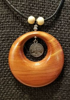 """2 1/4"""" diameter eastern red cedar pendant on adjustable black leather necklace. By the Woodchuck of Woodburn. Driftwood Jewelry, Wooden Jewelry, Resin Jewelry, Pendant Jewelry, Leather Necklace, Leather Jewelry, Red Cedar, Handmade Wooden, Urban Jewelry"""