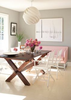 Beautiful dining space featuring a light pink couch, a picnic-style dining table, white film director chairs and pink flowers | Pierce Allen