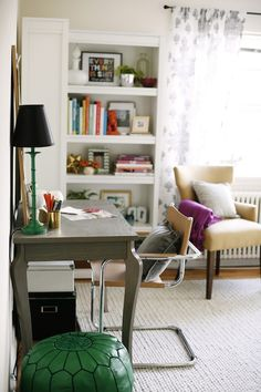 Pretty design with perfectly styled bookcases in the corner. Next to the gauzy gray and white draperies sits an upholstered chair with plum pink throw and accent pillow. Against the wall sits a gray desk paired with a chrome and leather directors chair. Atop the desk rests a leaning memo board, brass pencil holder and emerald green desk lamp with a black shade.