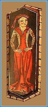 Figura de una mujer de pie, con las manos apoyadas en las caderas y coronada la cabeza con una diadema de la que penden dos cordones. Viste pellote rojo sobre gonela aprestada de color malva catedral de Teruel