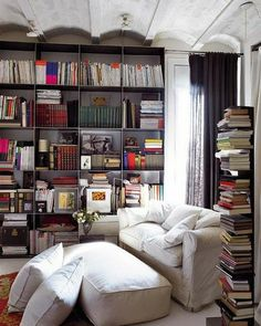 now, this looks like my kinda room. a fabric couch that is mostly pillows, surrounded by books. here is the question, where did that GIANT CUSHION of an ottoman come from? because i need it - urgently.