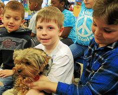 """Sammy the Yorkshire terrier, owned by Sheri Murphy, comes into Cooley Elementary School in Waterford to hang out with kids during their """"Cooley Crew"""" gatherings every three weeks. On March 23, Sammy chummed with Jayden Bilodeau, 6, left, Logan Goss, 5, center, and John Calhoun, 7, right, during a 30-minute reading time. Through the Crew Council, students have organized food drives, book drives and letter-writing campaigns to soldiers and seniors. Photo by Carol Hopkins, The Oakland Press."""