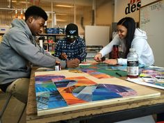 Youth artist/designers from Artists For Humanity's 3D Design Studio working on custom wall art for Boston Community Capital