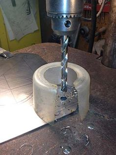 Simple drill press chip shield made from the bottom of a plastic jar.