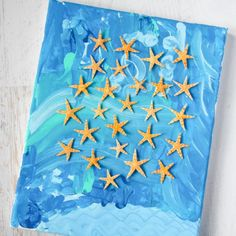 A gorgeous, open-ended project for kids, use your beach momentos & blue paint to make this unique wall art to hang with your travel pictures