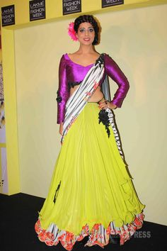 Mahie Gill was a stunner in a magenta choli top with a canary yellow lehenga skirt and printed dupatta at the Lakme Fashion Week press conference. #Style #Bollywood #Fashion #Beauty