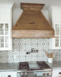 Pattern kitchen backsplash and wooden hood