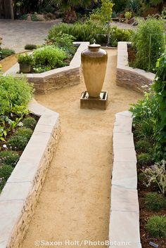 Stone raised bed vegetable beds in California front yard garden, with crushed rock path and urn water feature