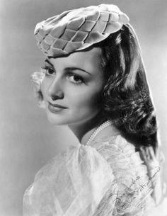 Olivia de Havilland sports an unusual pillbox hat made from woven velvet ribbons.
