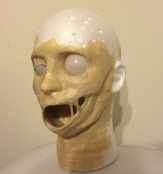 Masking tape, styrofoam head & cardboard to create a jaw. It comes down to layers.