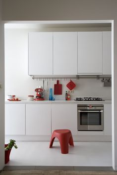 Photographer Bieke Claessens captured this monochromatic kitchen with pops of red beautifully!
