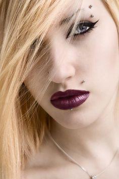 Body piercing studs on lips and eyebrow