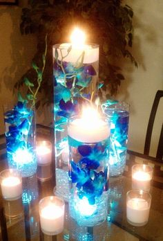 blue orchids submerged in vases filled with water and floating candles on the…