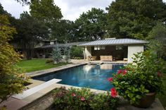 Brick and Flagstone Accents  If you lived here, your summer vacation destination would only be a few steps away. With its idyllic garden setting, this pool and outdoor living room are distinguished by the Oklahoma flagstone decking, standing seam metal roof and painted brick to match the house.
