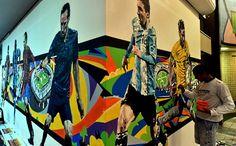 Comemoração da Copa do Mundo da FIFA Brasil. 2014. Grafiti em uma parede no perímetro do Aeroporto de Congonhas, em São Paulo, SP, Brasil. Paulo Consentino. Um artista pode ser visto dando retoques na obra.  Fotografia:  AFP.