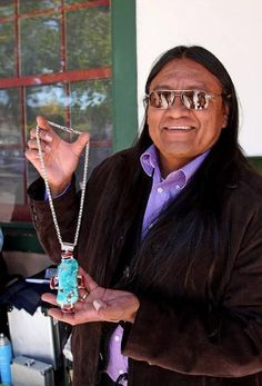 Rodey Lee Guerro - Navajo Jeweler, Albuquerque, NM showing off a large exquisite turquoise necklace