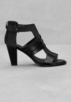 A pair of mid heel leather sandals featuring multiple straps of varying widths and textures.