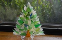 Sea Glass Tree: I start this tree with a piece of lucite shaped like a Christmas tree, then I use clear, flat sea glass to create a flat glass back.I also overlap pieces