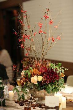 会場は和の雰囲気を取り入れたモダンな和洋折衷な空間。装花は高さのある枝ものを中心に、和風になりすぎないよう淡いピンクのバラを入れて洗練された雰囲気に。「高砂の左右には紅葉樹の柱を作って華やかに、野外の雰囲気を演出してもらいました」。 招待状で使ったリボンに合わせてテーマカラーはブラウンに。ゲストをお出迎えするウエルカムボードは安田さんの双子のお姉さんが描いてくれたそう。「ふたりの家紋&... Japanese Wedding, Japanese Modern, Floral Centerpieces, Flower Arrangements, Head Table Wedding, Something Beautiful, Autumn Wedding, Ikebana, Wedding Flowers