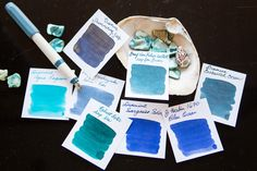 Fountain pen inks in a deep sea themed flat lay of teal and blue fountain pens, notebooks, and ink.