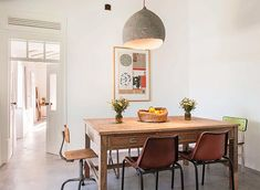 interesting pendant lamp over wood dining table with mismatched chairs at pensão agrícola. / sfgirlbybay