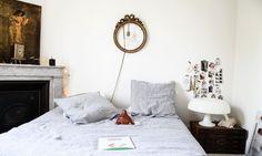Chambre parentale, lampe Nessino blanche, linge de lit Linge Particulier Marine rayée, masque posée sur le lit My Little Day, miroir rond vintage au dessus du lit. A découvrir sur The Socialite Family.