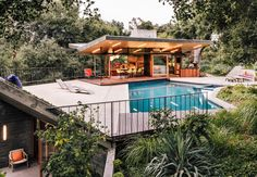 Creative Revival of a Modernist Gem - Photo 3 of 14 - Rising from the edge of the pool deck, a planted overhang shelters a gym and sauna below.