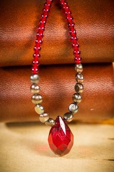 Closeup jewelry photography of a red and silver necklace.