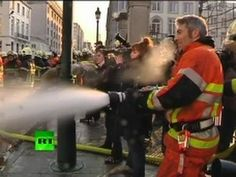Firefighters are on strike in Belgium and have been hosing down the police who are protecting the Prime Minister's office in Brussels.